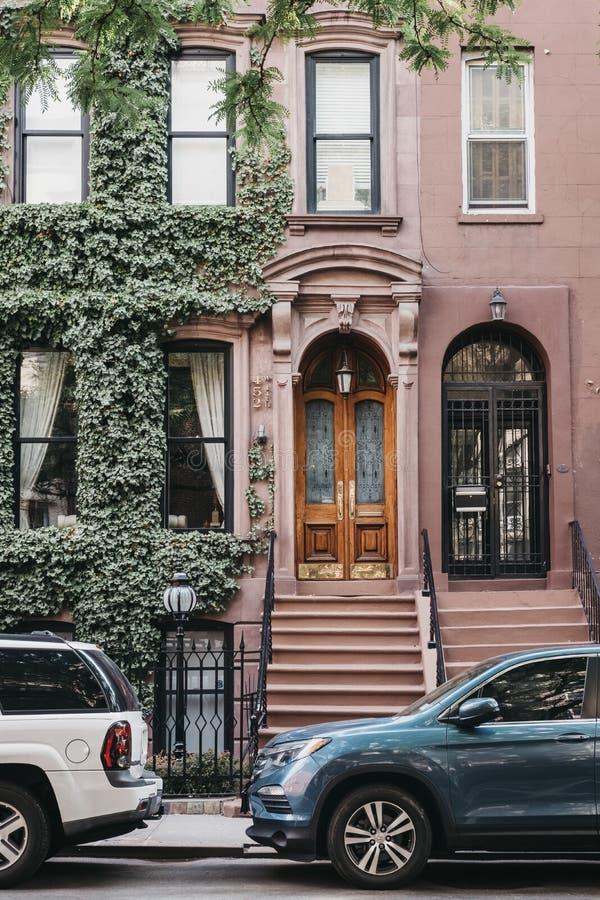 Фасад типичного дома Нью-Йорка с поклоном, парк автомобилей снаружи стоковые изображения rf
