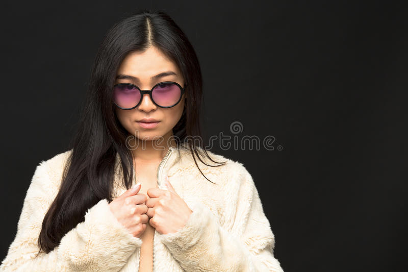 Фасонируйте азиатскую модельную женщину в солнечных очках в студии стоковая фотография