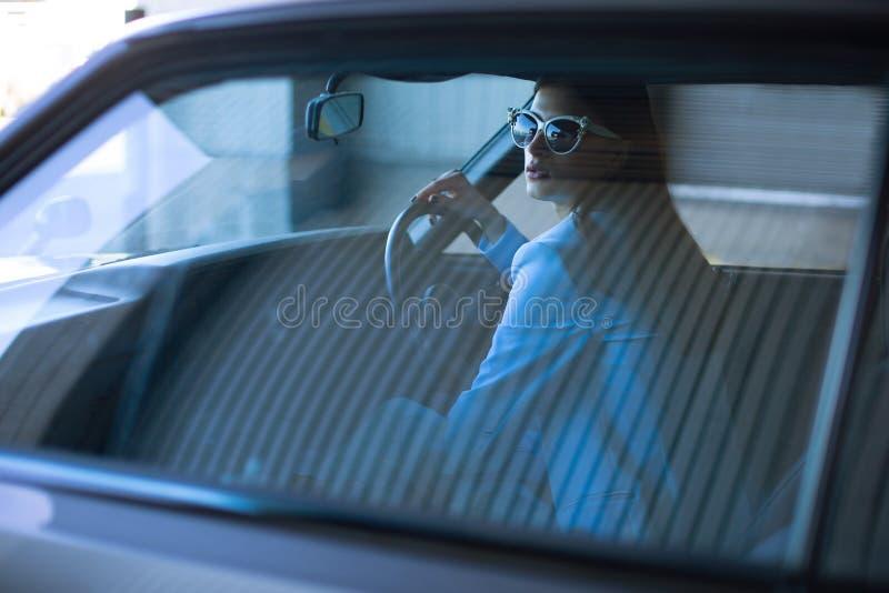 Фасонируйте даму управляя автомобилем в голубом костюме Стильная девушка сидя в автомобиле и лежа на управлении рулем whee стоковая фотография rf
