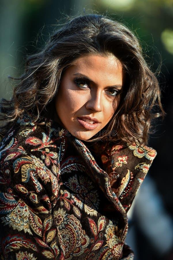 Фасонируйте внешний портрет красивой молодой женщины представляя в солнечном парке осени стоковое изображение rf