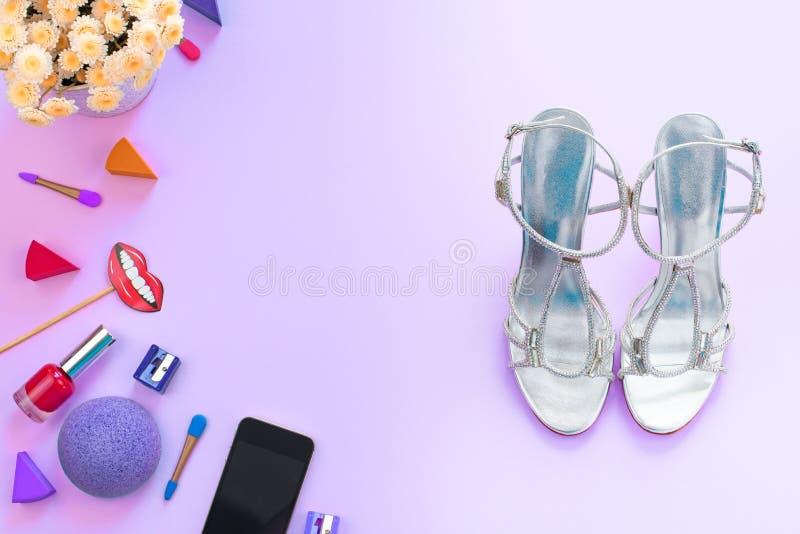 Фасонируйте женщинам устройство ботинок косметик аксессуаров передвижные цветки на фиолетовом космосе экземпляра положения кварти стоковое изображение