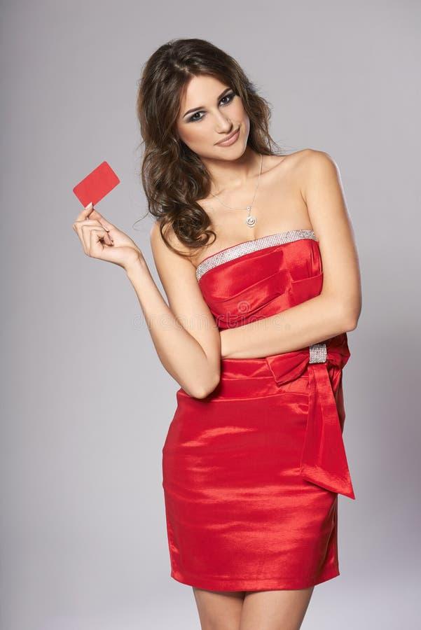 Фасонируйте женщину в красном платье показывая красную карточку стоковые фотографии rf