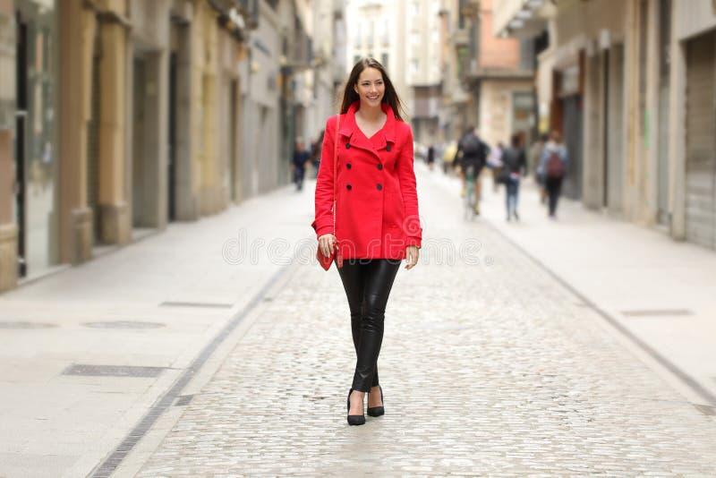 Фасонируйте женщину в красный идти на улицу города стоковые изображения