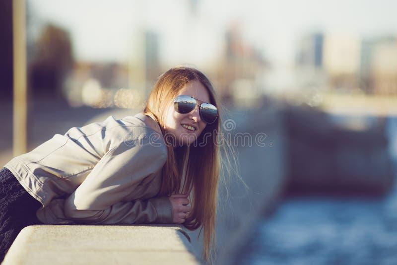 Фасонируйте женщину в солнечных очках на обваловке реки детеныши портрета красивейшей девушки напольные Счастливый ci солнечного  стоковое фото rf