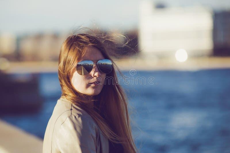 Фасонируйте женщину в солнечных очках на обваловке реки детеныши портрета красивейшей девушки напольные Счастливый ci солнечного  стоковое фото