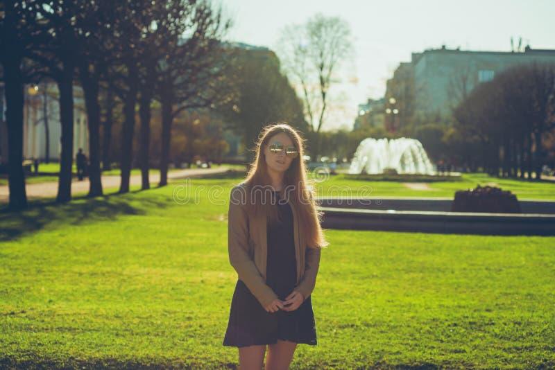 Фасонируйте женщину в солнечных очках на обваловке реки детеныши портрета красивейшей девушки напольные Счастливый ci солнечного  стоковое изображение
