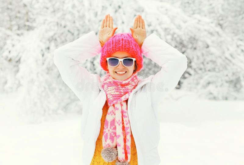 Фасонируйте женщину зимы усмехаясь нося красочный связанный шарф шляпы имея потеху показывая кролика ушей над снежной предпосылко стоковые фотографии rf