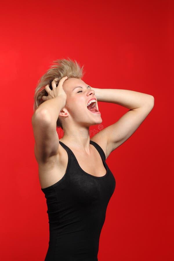 Фасонируйте женщину крича с ее руками на голове стоковая фотография