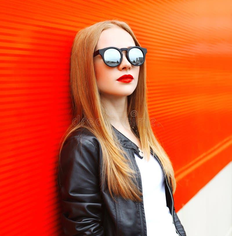 Фасонируйте женщину портрета нося куртку и солнечные очки черноты утеса над красным цветом стоковая фотография
