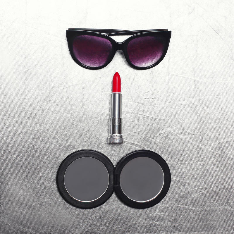 Фасонируйте комплект женщины, черные солнечные очки, губную помаду и меньшее карманное зеркало на текстурированном серебре стоковое фото rf