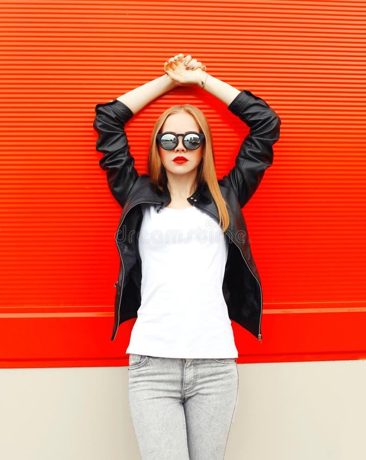 Фасонируйте милую женщину нося куртку и солнечные очки черноты утеса в городе над красным цветом стоковая фотография rf