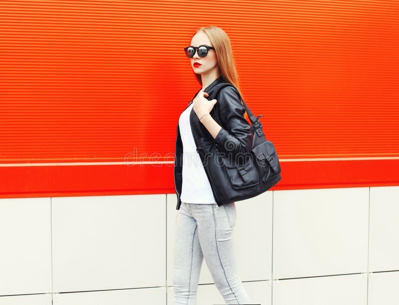 Фасонируйте милую женщину нося куртку, солнечные очки и сумку черноты утеса в профиле над красным цветом стоковые фотографии rf