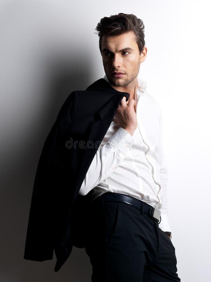 Фасонируйте молодому человеку в белых владениях рубашки черную куртку стоковое изображение rf