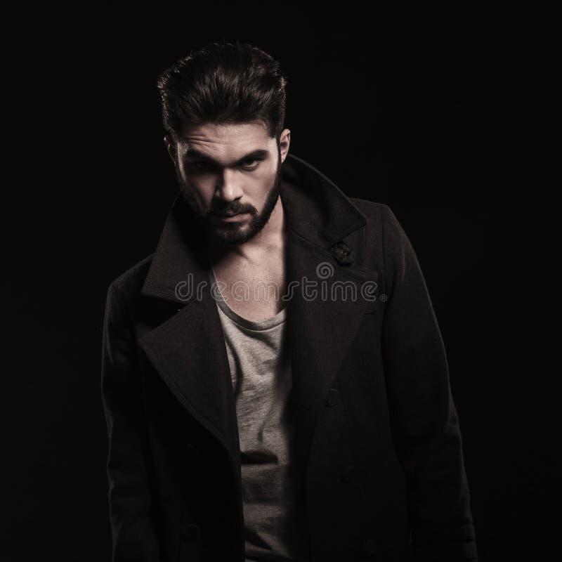 Фасонируйте молодого бородатого человека нося длинное пальто с большими воротниками стоковые фотографии rf
