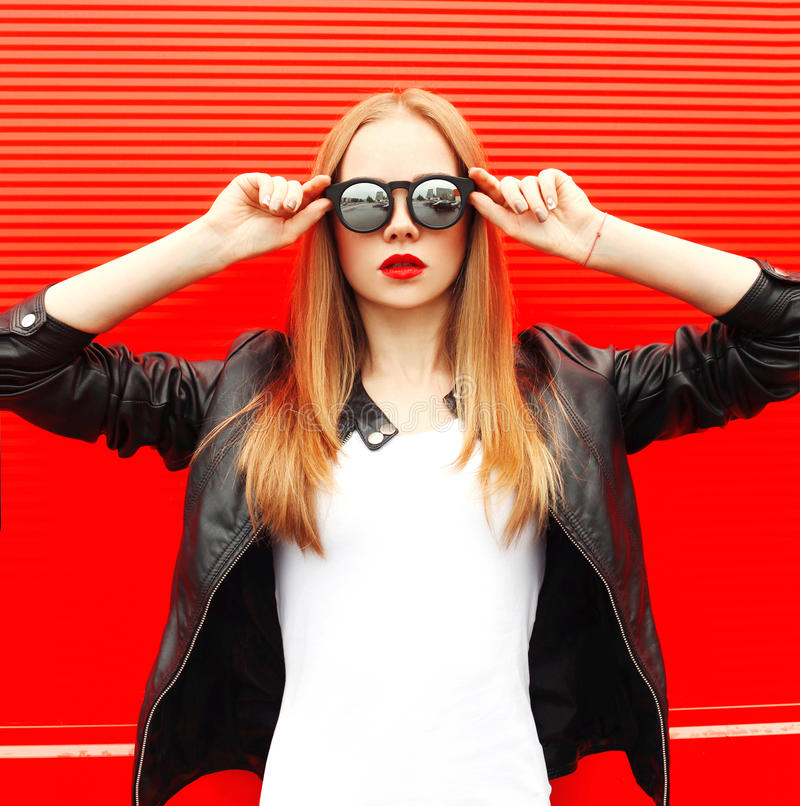 Фасонируйте молодую женщину портрета нося куртку и солнечные очки черноты утеса над красным цветом стоковое фото