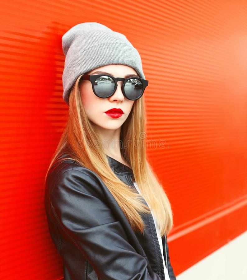 Фасонируйте носить женщины портрета солнечные очки, шляпу над красным цветом стоковые фотографии rf