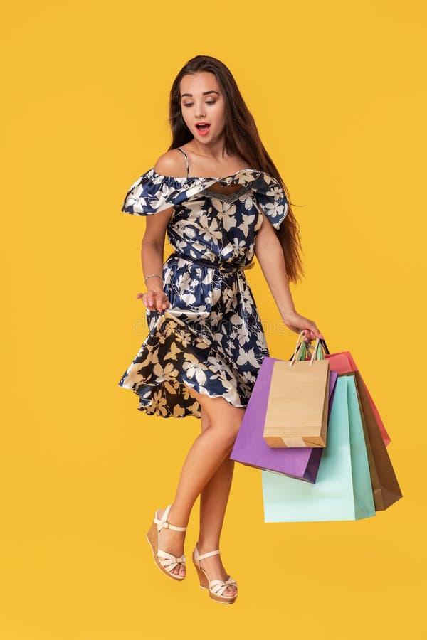 Фасонируйте носить молодой женщины портрета хозяйственные сумки, соломенную шляпу, платье представляя над красочной желтой предпо стоковые изображения