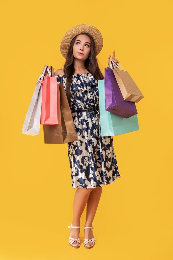 Фасонируйте носить молодой женщины портрета хозяйственные сумки, соломенную шляпу, платье представляя над красочной желтой предпо стоковая фотография rf
