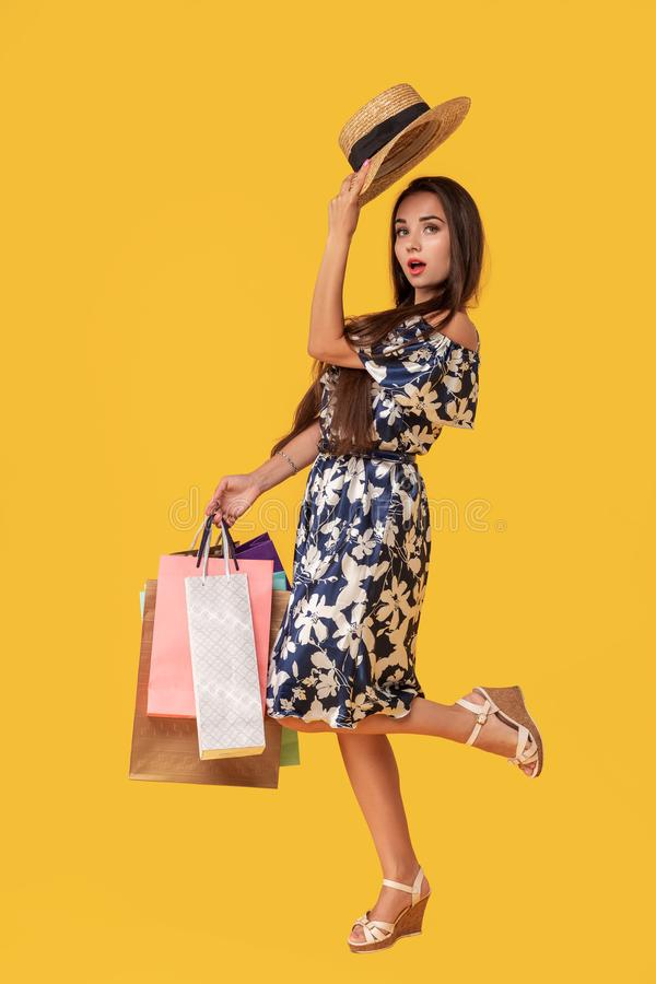 Фасонируйте носить молодой женщины портрета хозяйственные сумки, соломенную шляпу, платье представляя над красочной желтой предпо стоковые фотографии rf