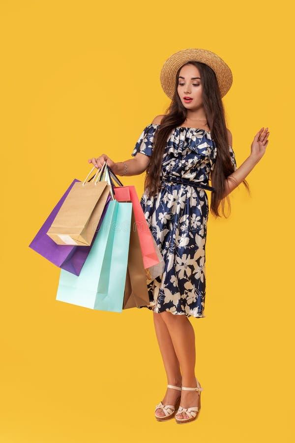 Фасонируйте носить молодой женщины портрета хозяйственные сумки, соломенную шляпу, платье представляя над красочной желтой предпо стоковое фото