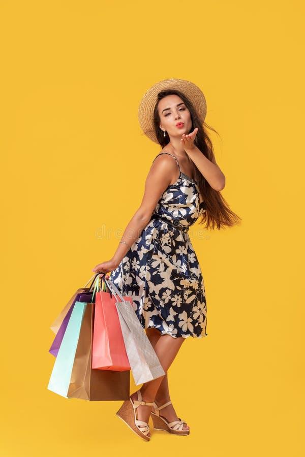 Фасонируйте носить молодой женщины портрета хозяйственные сумки, соломенную шляпу, платье представляя над красочной желтой предпо стоковое изображение rf