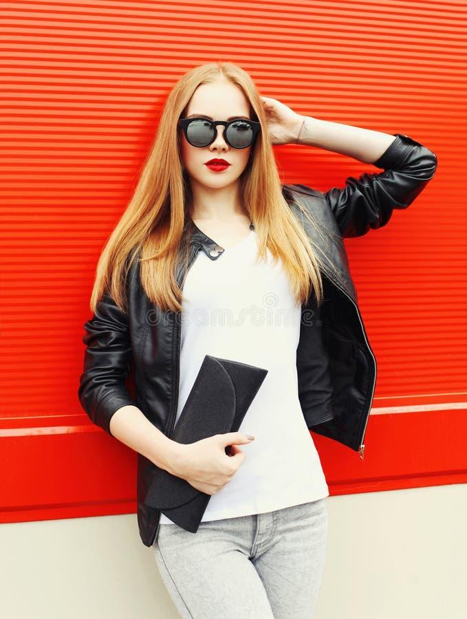 Фасонируйте довольно белокурую женщину нося куртку черноты утеса, солнечные очки и муфту сумки над красным цветом стоковое изображение