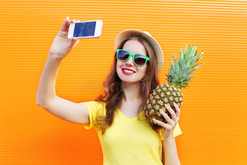 Фасонируйте довольно холодную девушку в солнечных очках, шляпу при ананас принимая selfie изображения на smartphone над красочным стоковое изображение