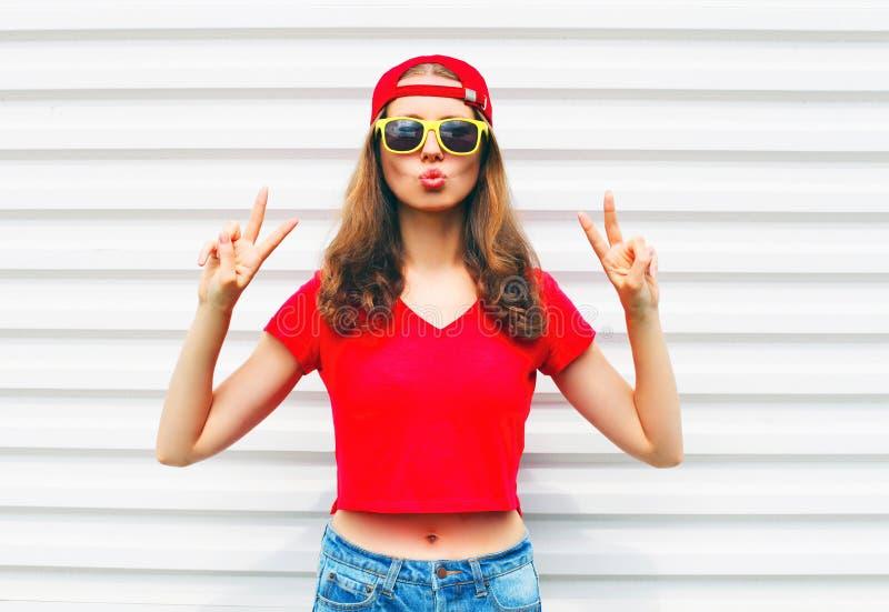 Фасонируйте довольно холодную женщину в солнечных очках и красной футболке над белизной стоковые фото