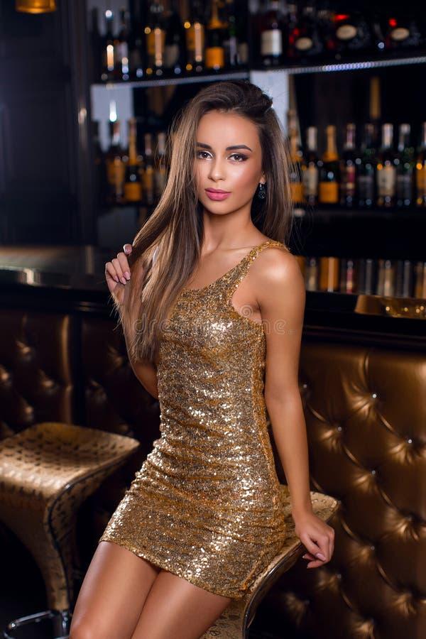 Фасонируйте портрет красивого брюнет в золотом сияющем платье с ярким составом стоковое изображение