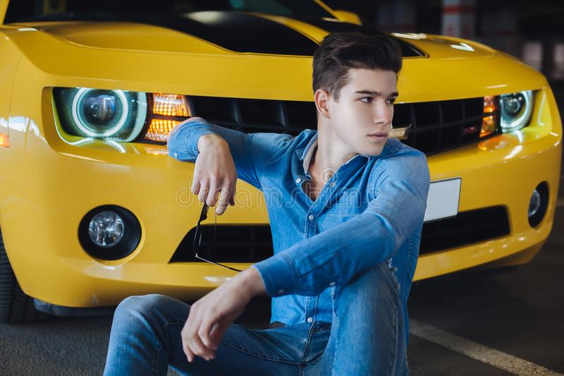 Фасонируйте портрет красивого человека сидя около современной желтой спортивной машины Способ самомоднейше рекламировать стоковые изображения rf