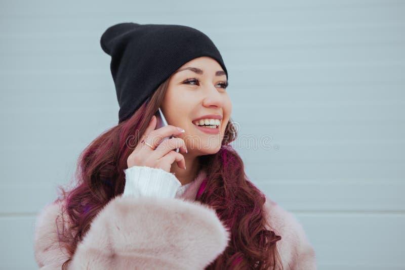 Фасонируйте портрет милой усмехаясь женщины битника в пальто норки и smartphone против красочной серой стены говорить стоковая фотография rf