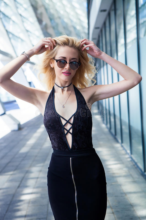 Фасонируйте портрет молодой элегантной белокурой женщины внешней солнечные очки, чокеровщик, черная юбка и сексуальная черная вер стоковое изображение
