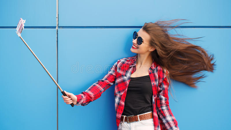 Фасонируйте портрет довольно усмехаться и женщину в солнечных очках с smartphone против красочной голубой стены Сделайте selfie стоковые изображения rf