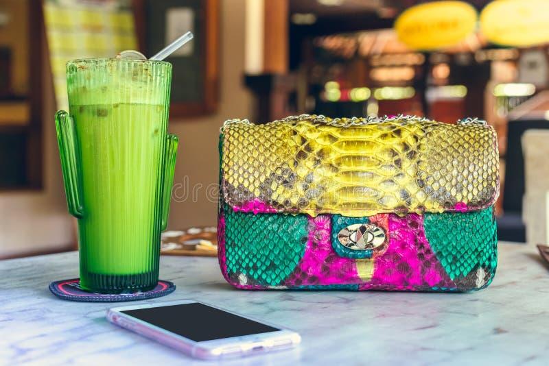 Фасонируйте роскошную сумку питона snakeskin на деревянном столе в ресторане Остров Бали стоковая фотография rf
