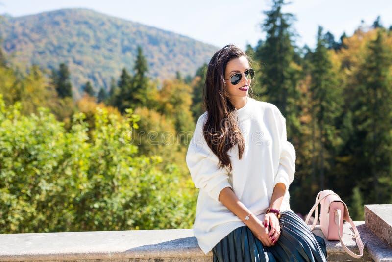 Фасонируйте солнечные очки красивого портрета женщины нося, белый свитер и зеленую юбку стоковая фотография