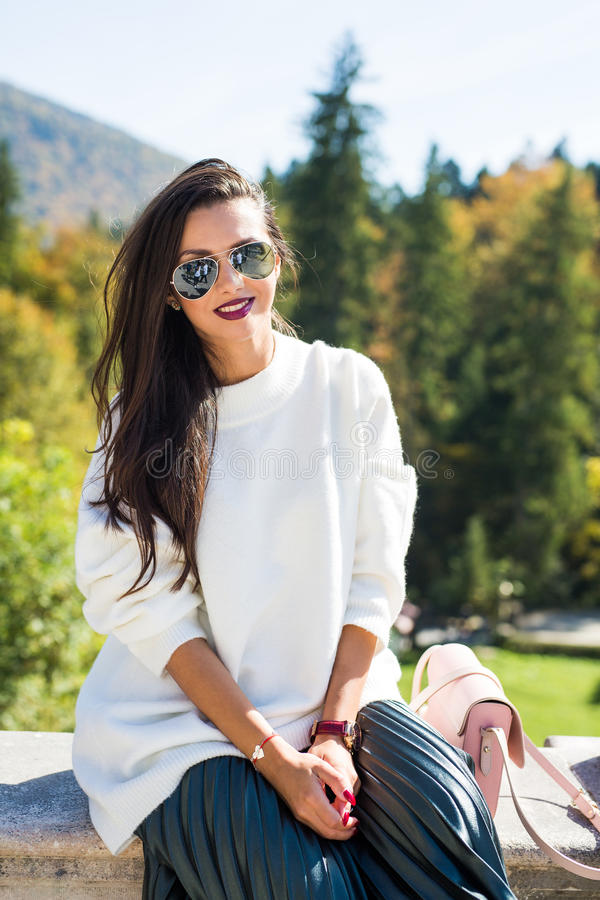 Фасонируйте солнечные очки красивого портрета женщины нося, белый свитер и зеленую юбку стоковые фотографии rf