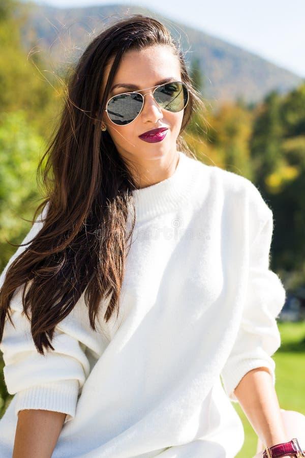 Фасонируйте солнечные очки красивого портрета женщины нося, белый свитер и зеленую юбку стоковые фото