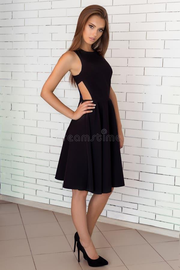 Фасонируйте съемку красивой сексуальной девушки в черном платье на предпосылке стены кирпича белой в студии стоковое фото