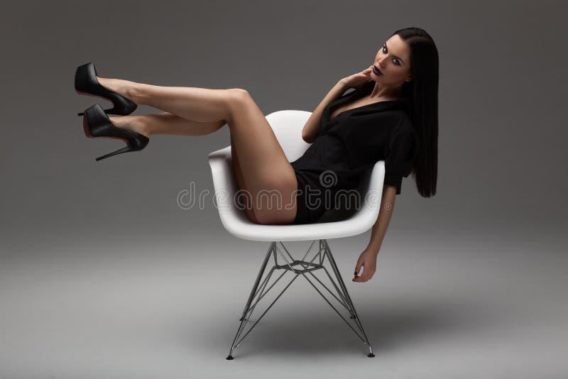 Фасонируйте съемку красивой сексуальной женщины брюнет при длинные прямые волосы, черная рубашка и черные ботинки сидя на стуле стоковая фотография rf