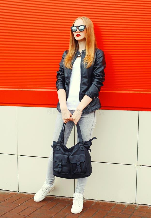 Фасонируйте утесу женщины нося черные куртку, солнечные очки и сумку над красным цветом стоковое фото rf
