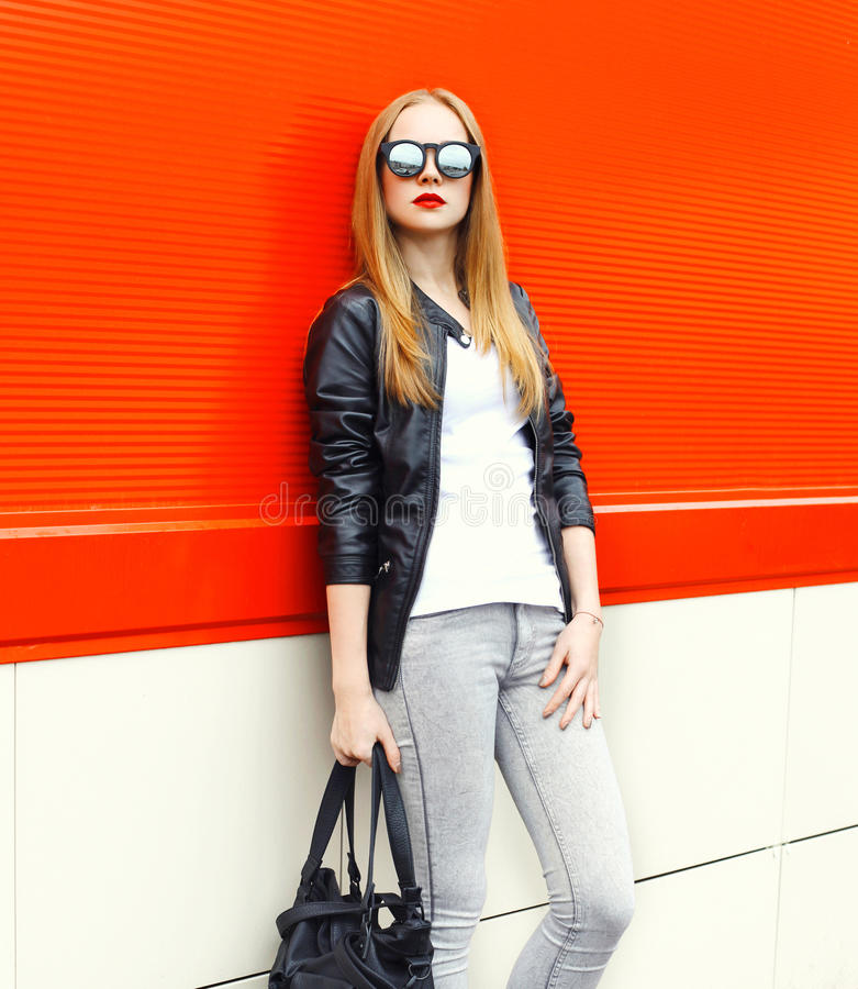 Фасонируйте утесу милой женщины нося черные куртку, солнечные очки и сумку над красным цветом стоковое изображение rf