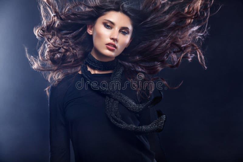 Фасонируйте фото красивой молодой женщины в милом платье представляя над черной предпосылкой с дымом Фото моды с стоковые фотографии rf