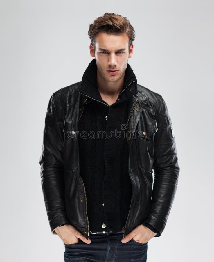 Фасонируйте человека, куртки модели кожаной, серой предпосылки стоковые изображения