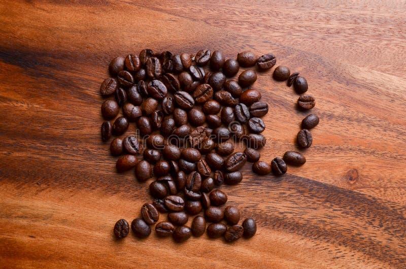 Фасоли чашки кофе на деревянной предпосылке стоковые фото