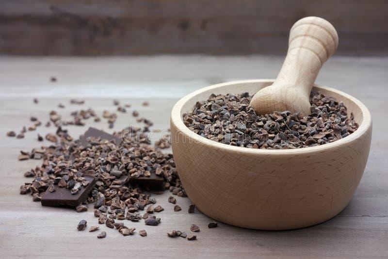 Фасоли nibs какао сырцовые задавленные в пестике стоковая фотография