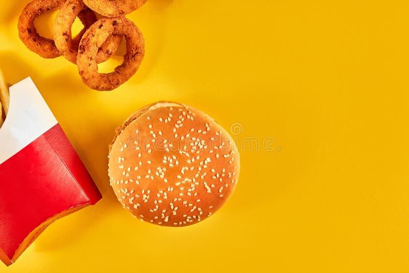 Фаст-фуд и нездоровая концепция еды - близкие вверх закусок фаст-фуда на желтой предпосылке стоковые изображения