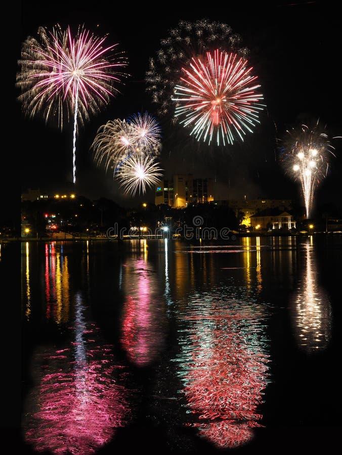 Фейерверки города отраженные в озере стоковое изображение