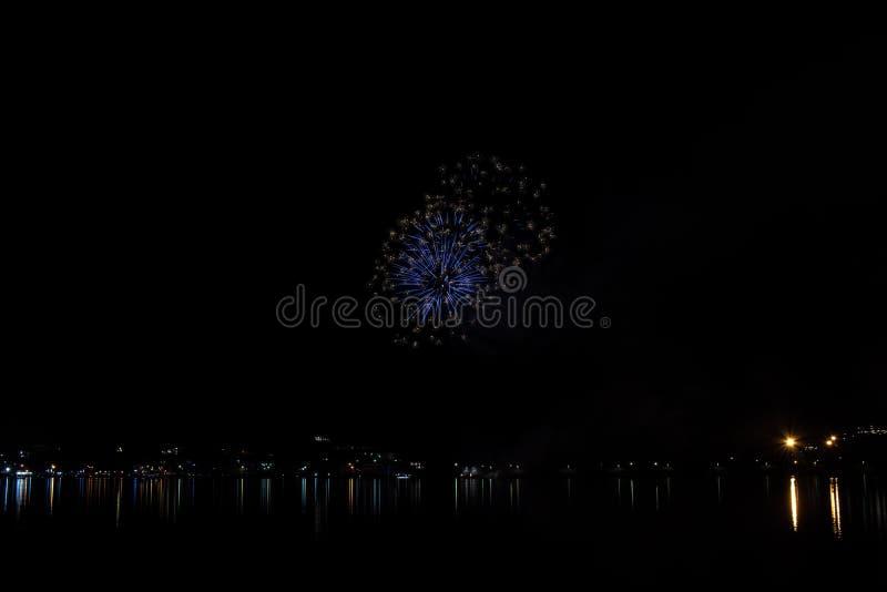 Фейерверки красят небо в различных цветах и отражены в озере Miseno, создавая захватывающую панораму стоковое изображение
