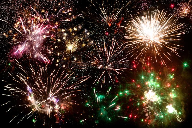 Фейерверки, много пестротканых вспышек салюта в ночном небе, праздничном знамени, плакате Нового Года, концепции поздравительной  стоковое изображение