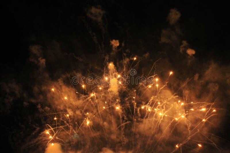 Фейерверки салют Гирлянда предпосылки неба фантастическая оранжевых сверкная светов в ночном небе во время Нового Года и рождеств стоковое изображение rf